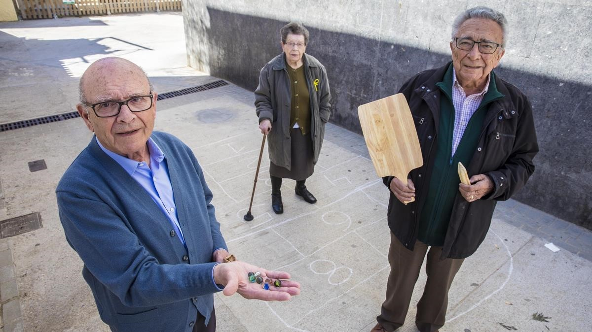 Josep muestra la tabla de cortar con la que juega al bèlit y el cilindro puntiagudo que segolpea.A la izquierda,Joan, con canicas. Al fondo,Concepció sobre una xarranca. Los tres, de 88 años, enseñan los juegos de su infancia por Youtube.