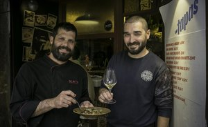 JordiPeris y Jordi Palomino, con unos pies de cerdo y una copa, en el bar El Pla.