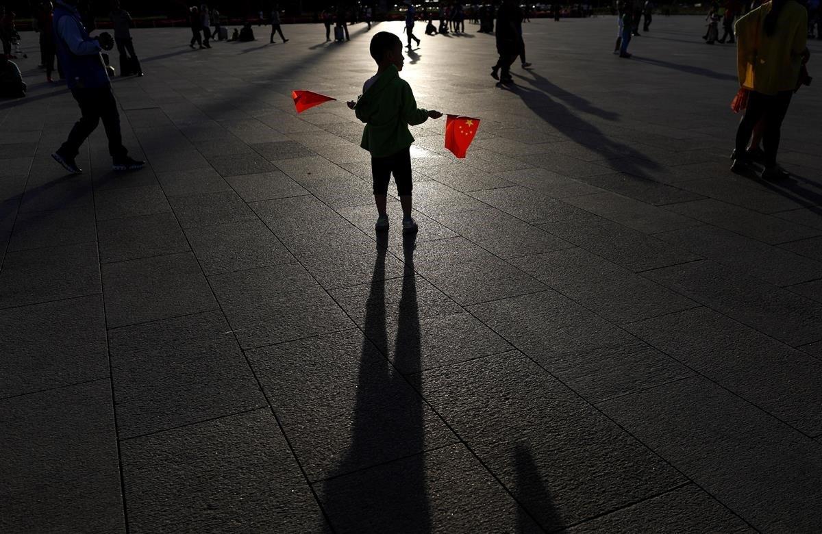 Un niño sostiene dos banderas en la plaza de Tiananmen en Pekín. El Gobierno de China afronta este martes uno de los aniversarios más dolorosos de su historia -el trigésimo desde la matanza de Tiananmen- sin asumir responsabilidades al negar las evidencias y criminalizando a las víctimas de la represión que acabó con la protesta estudiantil.