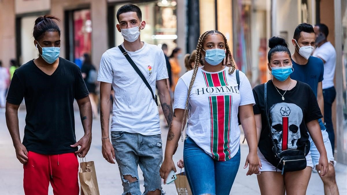 Jóvenes paseando por el Carrer Major, de Lleida, con mascarilla.