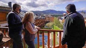 El vendedor de pisos de Finques PuigcerdàLluís Casanovas(derecha) muestra un piso a unos clientes, ayer.