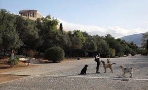 Una mujer da de comer a unos perros callejeros. Al fondo se ve el Partenón, en la antigua Acrópolis.