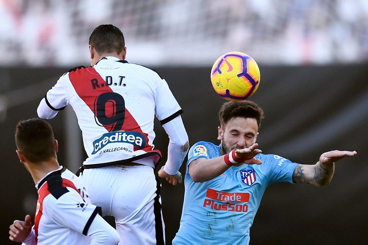 Saúl (d) remata un balón ante la oposición de Raúl De Tomás.