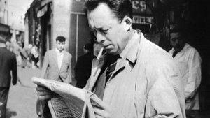 Albert Camus en 1959, leyendo el diario en las calles de París.