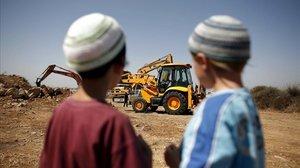 Dos niños judíos observan una retroexcavadora utilizada en la construcción de unas 50 viviendas en el asentamiento judío de Ariel .
