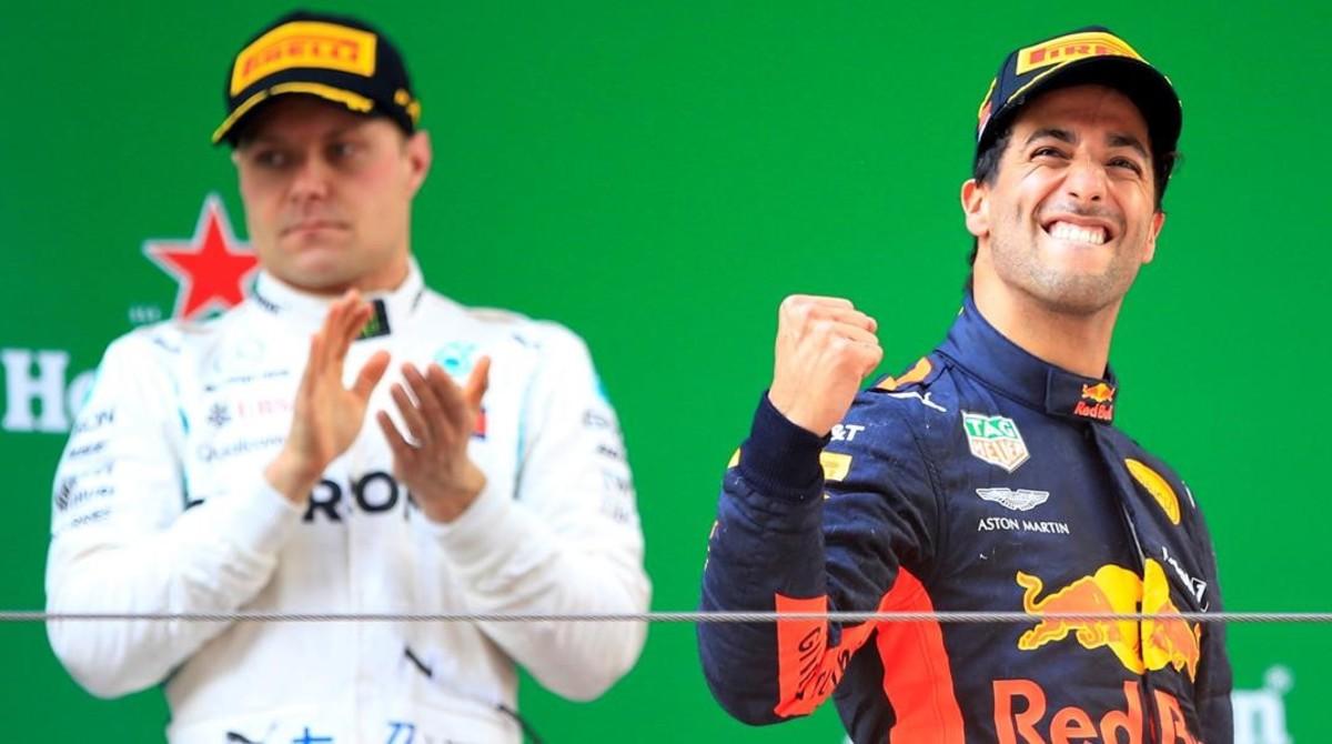 El australiano Daniel Ricciardo (Red Bull) celebra su victoria en China al subir al podio, ante el aplauso de Valtteri Bottas (Mercedes), segundo.