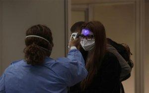 Personal médico toma la temperatura por el peligro del coronavirus.
