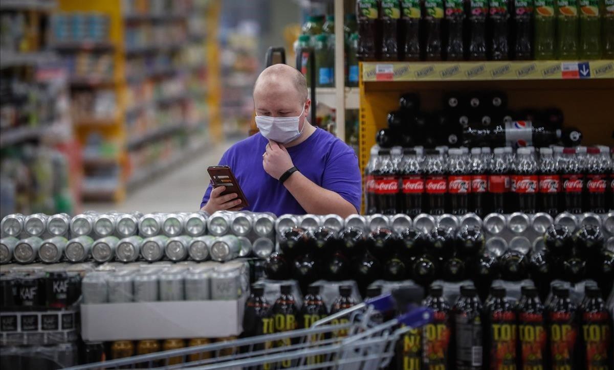 Un cliente revisa las estanterías de bebidas de un supermercado ruso.