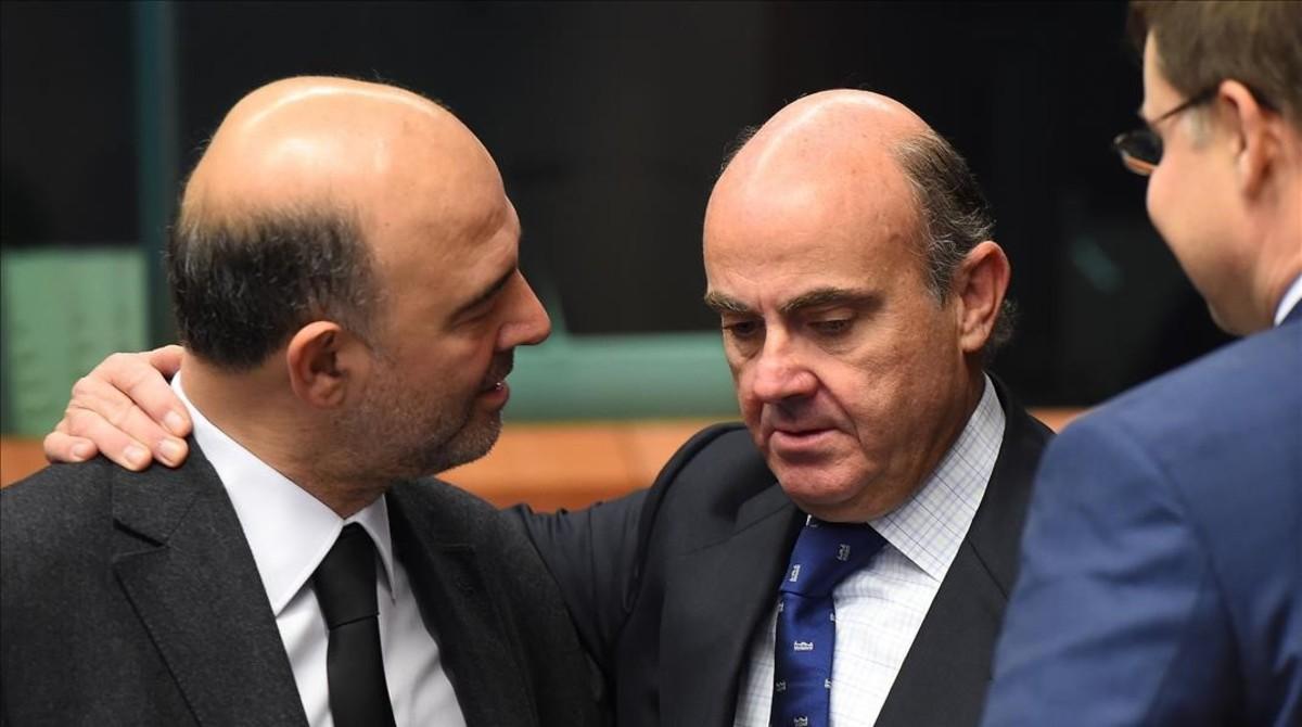 El ministro de Economía en funciones, Luis de Guindos, y el comisario de Asuntos Económicos, Pierre Moscovici, en presencia del vicepresidente de la Comisión Valdis Dombroskis, en un imagen de archivo.