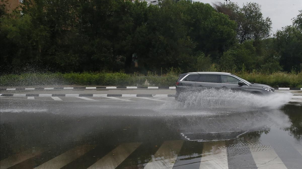 Un coche circula por una calle de Madrid inundada.