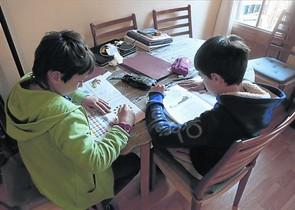 Deberes 8 Dos niños de quinto de primaria hacen sus tareas escolares.
