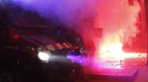 Un coche de los Mossos, junto a unos contenedores en llamas.