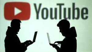 Dos usuarios pasan con sus portátiles frente a un logotipo de Youtube, en marzo pasado.