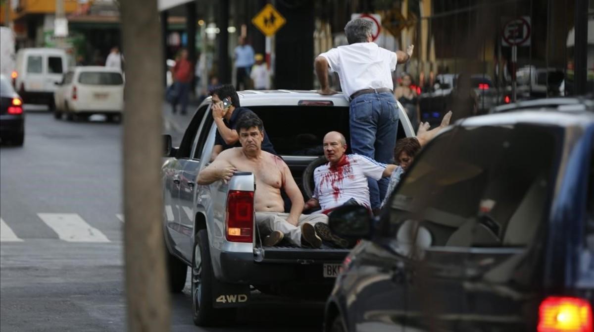 Efraín Alegre, líder del Partido Liberal (izquierda), junto a un herido en los disturbios de la madrugada del sábado en Asunción.