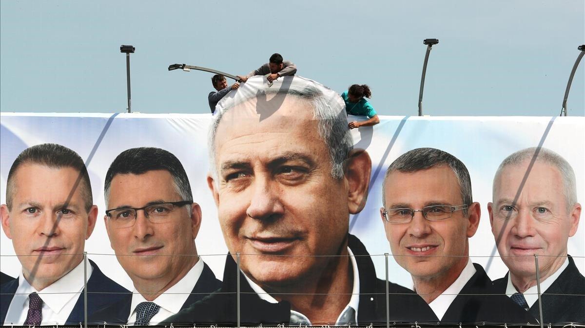 Un grupo de operarios trabajaen una valla publicitaria de propaganda electoral en la que aparece Netanyahu con candidatos de su partido, el Likud, en Jerusalén.