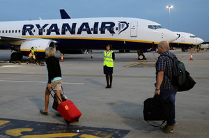 FILE PHOTO: People walk to board a Ryanair flight at Stansted Airport, northeast of London, Britain, September 7, 2017. Picture taken September 7, 2017. REUTERS/Kevin Coombs/File Photo