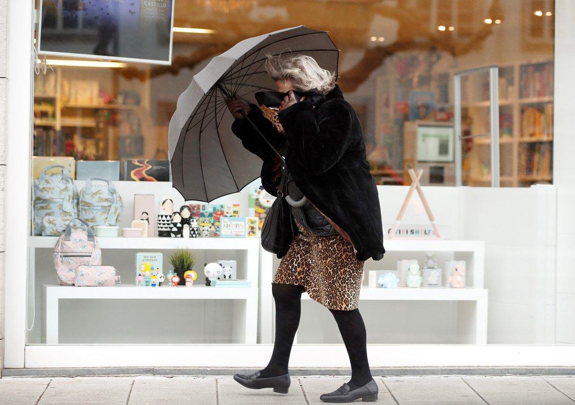 Una mujer se protege de la lluvia en Galicia.