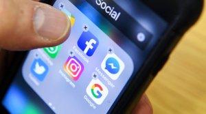 Un hombre organiza los iconos de varias redes sociales como Facebook, Instagram y Twitter en la pantalla de su móvil.