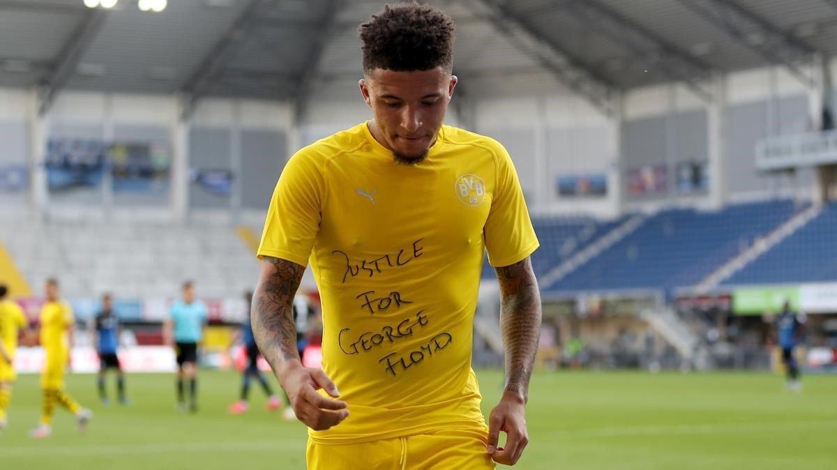 Jadon Sancho, del Borussia Dortmund, enseña una camiseta interior de apoyo a George Floyd, durante el partido ante el Padeborn.