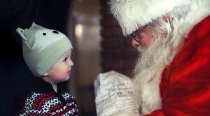 Un niño entrega su carta a Papá Noel.