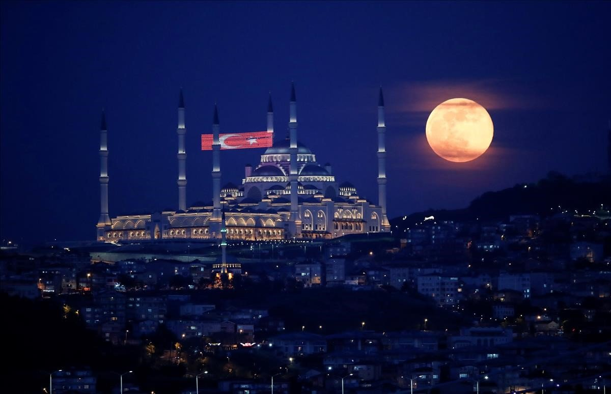 La luna llena se eleva sobre la Mezquita Camlica.