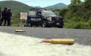 MEX23 ARTEAGA MEXICO 23 07 2013 - Agentes federales y soldados del Ejercito mexicano resguardan una carretera hoy martes 23 de julio de 2013 en el municipio de Arteaga en el estado mexicano de Michoacan donde se registro uno de los varios ataques contra oficiales federales ocurridos en este estado que dejo un saldo de al menos veinte presuntos narcotraficantes y dos policias muertos Entre las fuerzas federales hay quince heridos por estos ataques ademas de un numero no determinado de lesionados entre los comandos que atacaron a los policias EFE STR