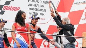 El mítico piloto italiano Giacomo Agostini le entrega el premio de vencedor, en Phillip Island, a Marc Márquez.