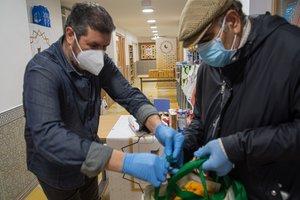 Mohamed reparte una bolsa de alimentos a un vecino en el Centre Cultural Islàmic de Sants.