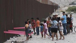 Niños juegan en un balancín situado en el muro de México a su paso por Ciudad Juarez.