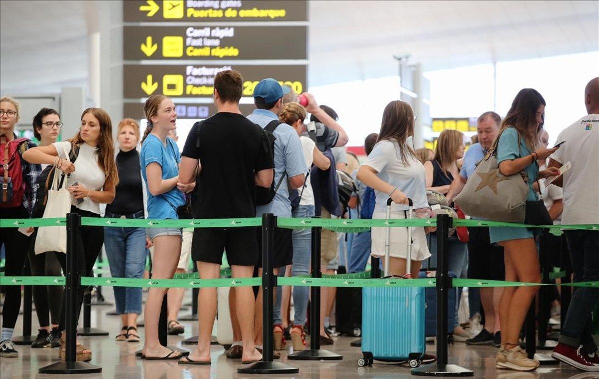 Pasajeros esperan para pasar los controles de seguridad en el aeropuerto de El Prat.