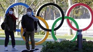 Dos personas pasean por Tokio junto a los aros olímpicos.