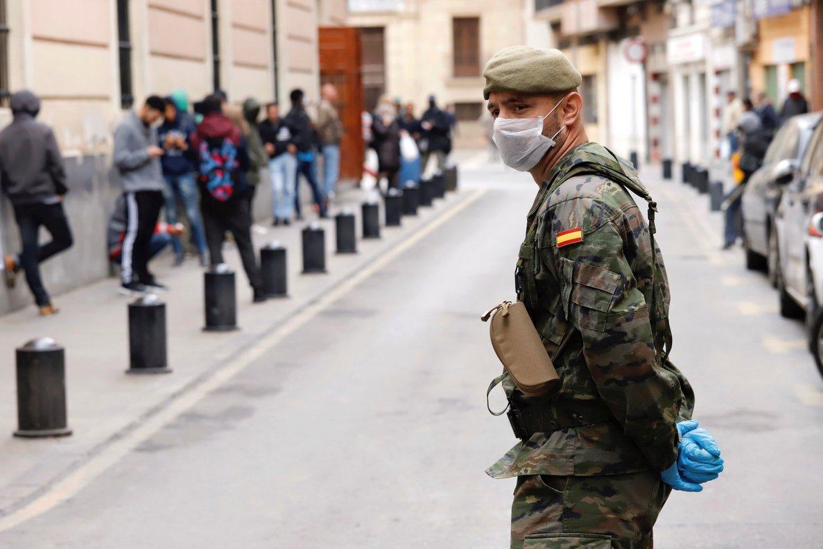 GRAF078. MURCIA, 21/03/2020.- Un militar del Ejército de Tierra mantiene orden ante un comedor social de la capital, durante la mañana del séptimo día de estado de alarma en Murcia. EFE/Juan Carlos Caval