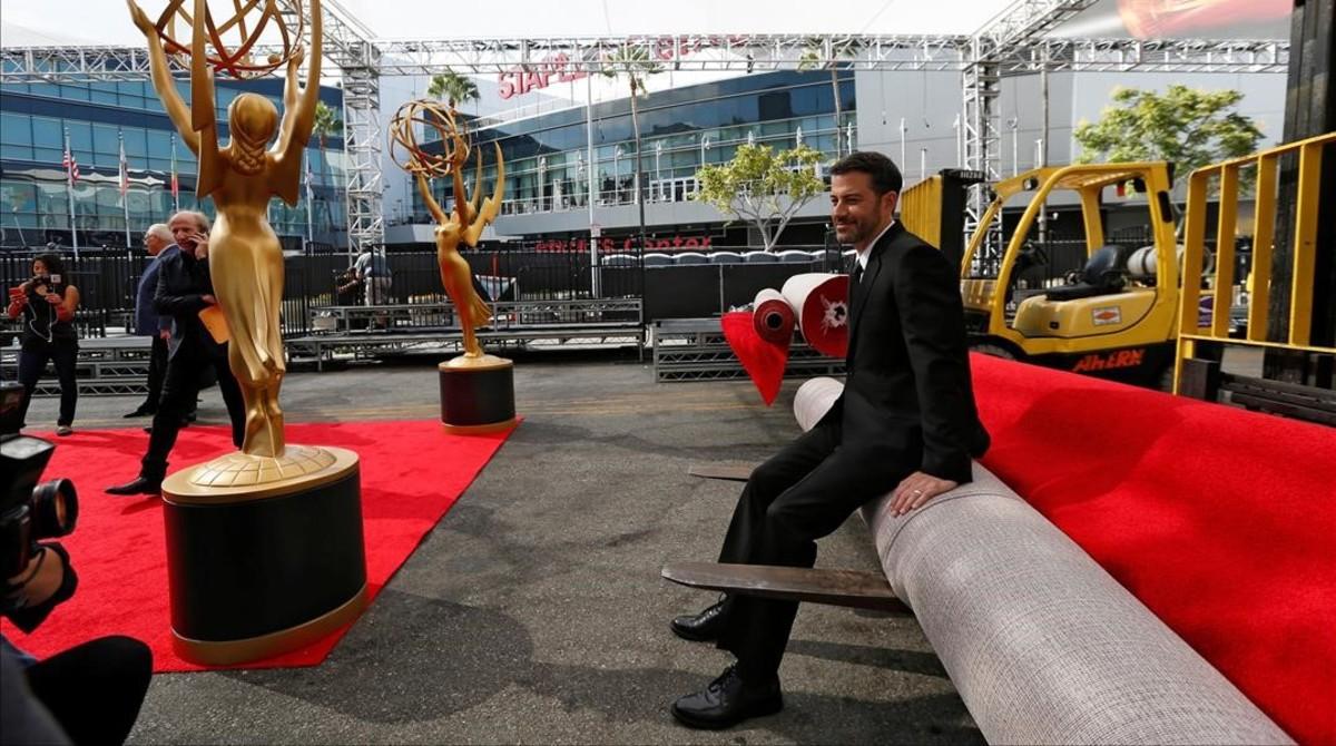 El presentador de la gala, Jimmy Kimmel, posa para la prensa, sentado sobre la alfombra roja de los68ºpremios Emmy, aún enrollada.