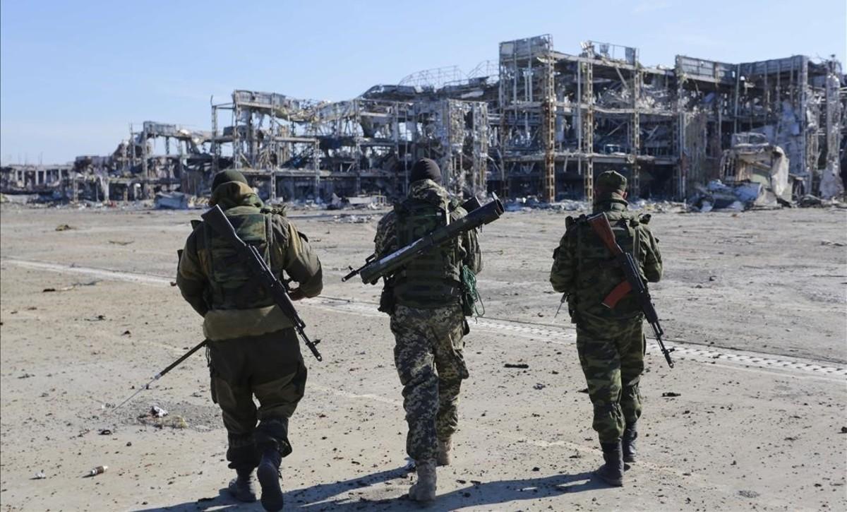 Tres soldados ucranianos prorrusoscaminan por el aeropuerto de Donetsk, destruido por la guerra en el 2015.