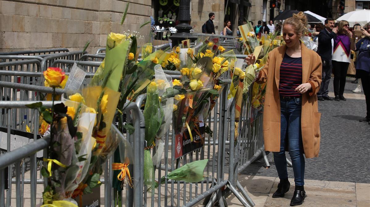 Una joven deposita rosas amarillas en las vallas ubicadas frente al Palau de la Generalitat.