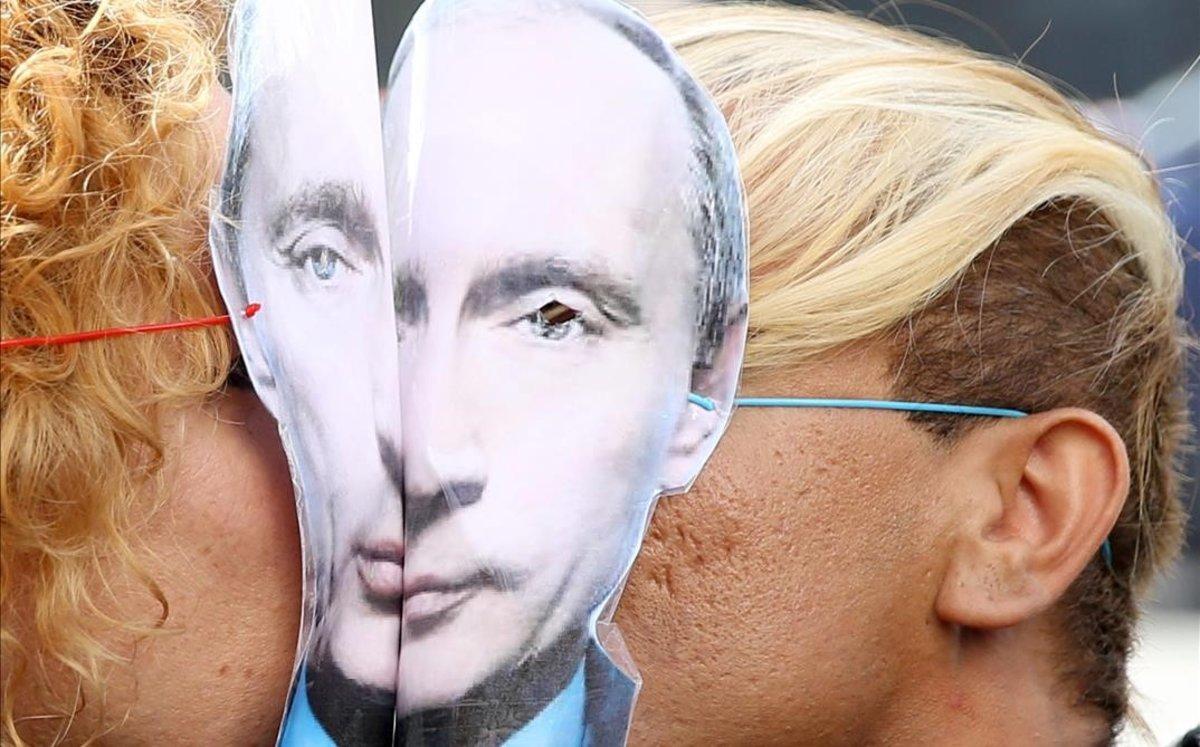 Una pareja se besa durante una protesta contra la discriminación de personas LGTBI con sendas caretas de Vladimir Putin.