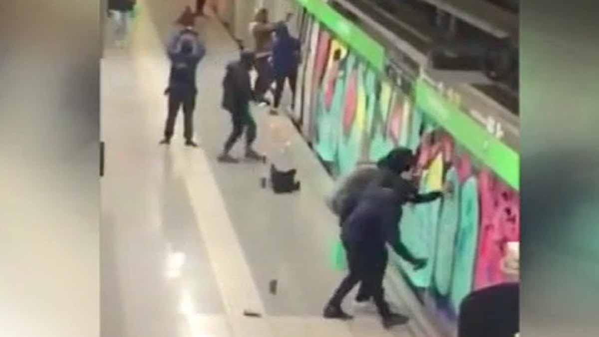 Una veintena de grafiteros pintanvariosvagones de dos convoyes de la línea 3 del Metro de Barcelona, ante la miradade los guardias de seguridad.