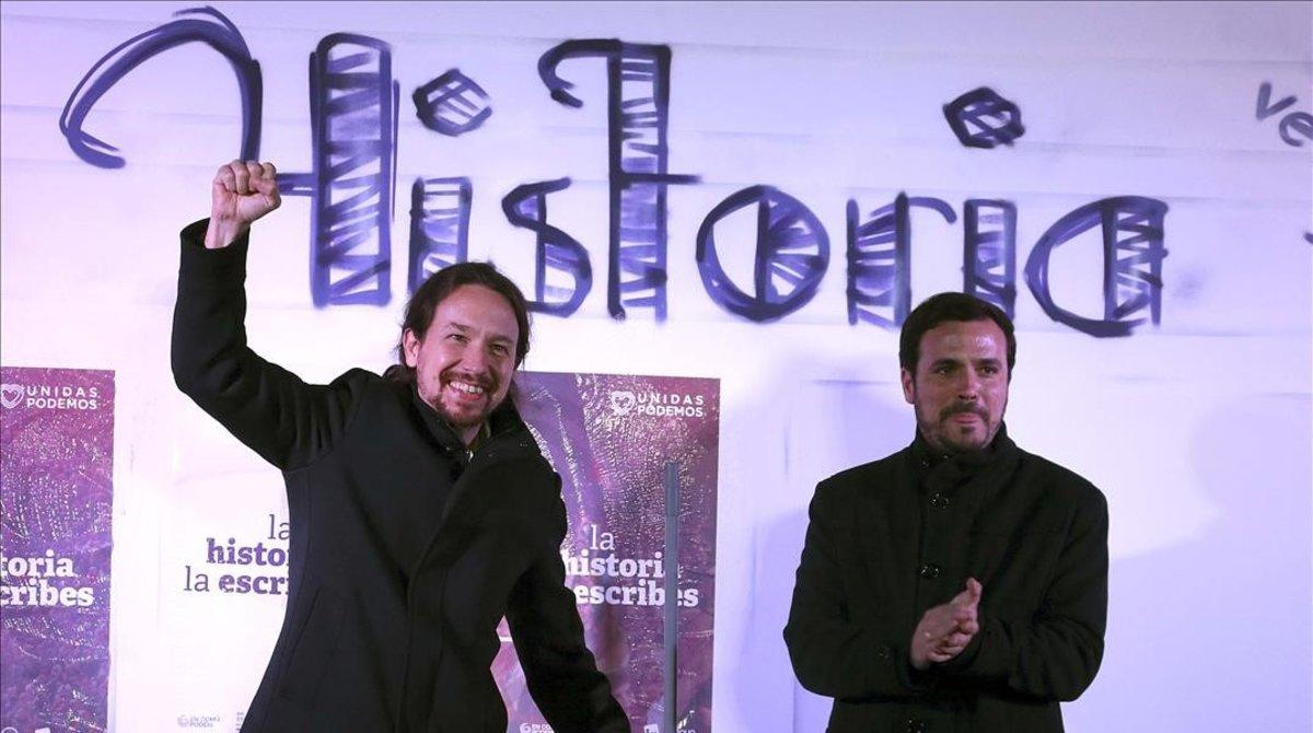 El secretario general de Podemos, Pablo Iglesias, y el líder de IU, Alberto Garzón, en la pegada de carteles en el distrito madrileño de Usera.