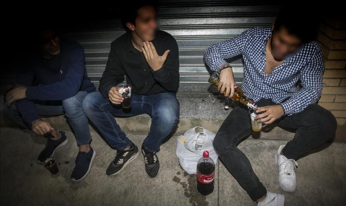 Unos chicos consumen alcohol en la calle en Mataró.
