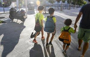 Unos niños se dirigen a un casal en Barcelona, acompañados por su padre, el verano pasado.