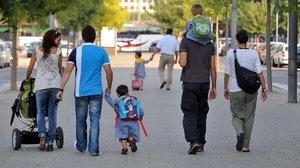 Unos padres llevan a sus niños al colegio.