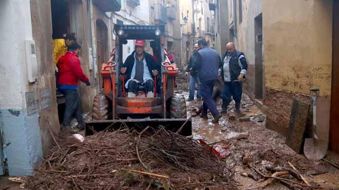 Vecinos y voluntarios de la Espluga de Francolí trabajan limpiar los efectos de las riadasde esta noche.