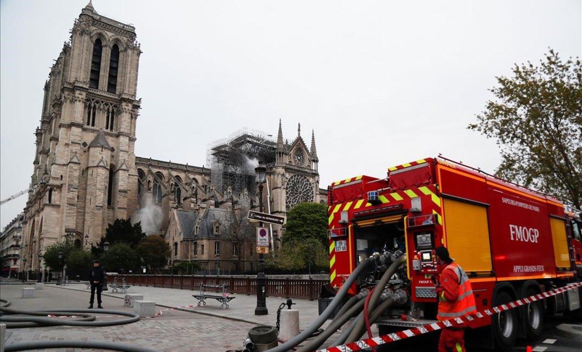 Bomberos ante Notre Dame, tras extinguir las llamas.