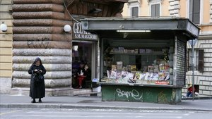 Una monja espera junto a un quiosco de prensa en Roma.