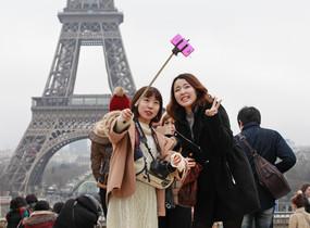 Turistas utilizando del palo para hacerse selfis en París.