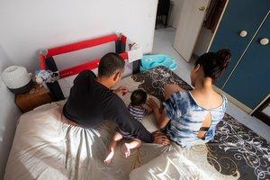 Claudia, Johnny y el pequeño Gareth, de cinco meses, que reciben ayuda de Cáritas,en la habitación en la que viven.