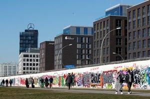 Personas caminando a la vera del terraplén del río Spree junto a los restos del Muro de Berlín, en la East Side Gallery de Berlín.