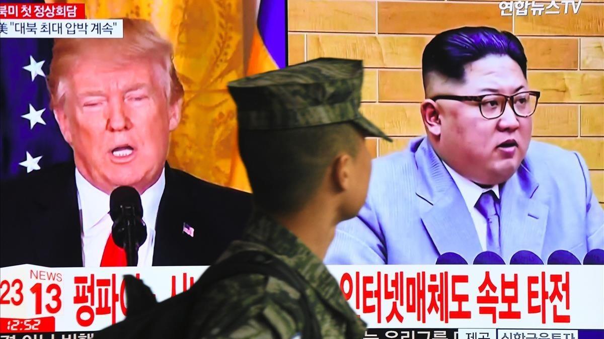 Un soldado surcoreano pasa frente a un televisor en Seúl mientras aparecen en la pantalla DonaldTrump y Kim Jong un.
