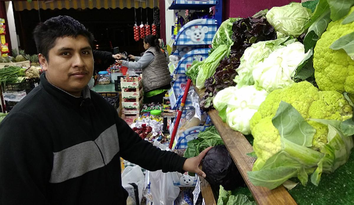 Éverson Fernández e Ibeth Kathia Suárez, al fondo, en su comercio de frutas y verduras de Barcelona.