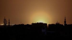 Foto tomada desde la ciudad de Duma, en la que se observan las llamas a distancia provocadas por la fuerte explosión en el aeropuerto internacional de Damasco, el 27 de abril.